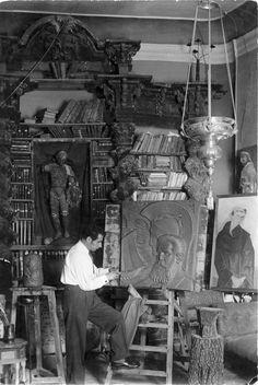 Imagen de Ramón Acín terminando de modelar la placa de Joaquín Costa en su estudio de la calle de las Cortes. Al fondo se aprecia su biblioteca y se ven también las obras ´Fraile´ y ´Rostros fantástico´.  Ramón Acín en su estudio / Autor: Fidel Oltra, Huesca / 1930