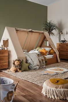 Spark a love of travel and nature with wild animal details – and even inspire imagination and play with a safari-themed bed.  The earthy tones in this room are classy but no less fun for young, enquiring minds, and a plant in the corner not only brings an element of nature into your child's space, but also helps improve air quality. #girlsbedroom #girlsbedroomideas #homedecor #bedroomdecorate #safaritimebedroom