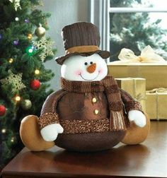 A rolly polly snowman with sweet face, dressed all up in warm colors.