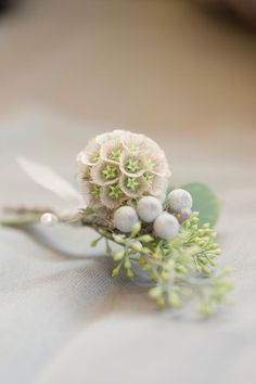 The men will wear boutonnieres of scabiosa pods, silver brunia and seasonal greenery