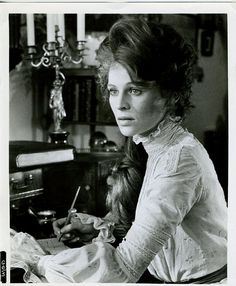 Julie Christie as Marian Maudsley (Lady Trimingham) writing among books in The Go-Between (1970). The story follows a young boy named Leo (Dominic Guard) who finds himself a 'go-between' caught up between Marian (Julie Christie), who is the daughter of his host, and a poor neighbor, Ted Burgess (Alan Bates) whom she loves.