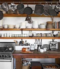 Open shelving with pots above the range. Brick wall behind??