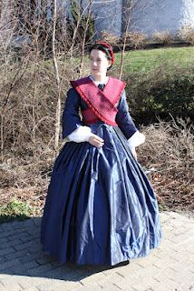 Blue day dress with narrow pagoda sleeves and a narrow red sontag or 'bosom friend'. Sharp outfit!