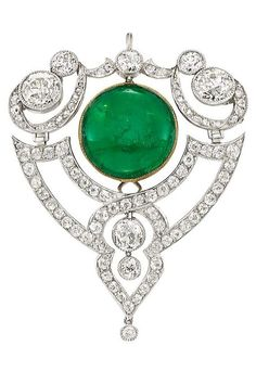 Gold, Diamond and Cabochon Emerald Pendant-Brooch, circa 1905. The openwork modified shield-shaped pendant-brooch centring one flexibly-set round cabochon emerald, highlighted by seven old European-cut diamonds, set throughout with 64 old-mine cut diamonds.