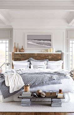 A grayscale bedroom with cozy textiles, wood headboard, and makeshift bench made with stacked books