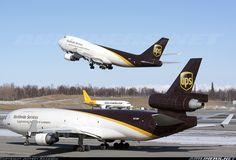 United Parcel Service (UPS) McDonnell Douglas MD-11(F) holding short, Boeing 747-400 taking off