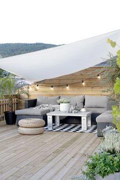 Terrasse bois aménagée sous un voile d'ombrage