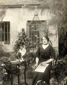 A beautiful garden portrait with several cannabis plants seen growing in the background, Paris, 1910.