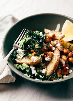 Harissa chickpea bowl with potatoes, lemon-y tahini, and greens is a lightly spicy, totally filling weeknight dinner option.
