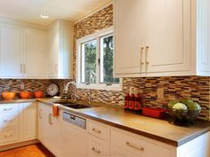 The long white cabinets in this kitchen allow the multi-shaded brown backsplash to shine.