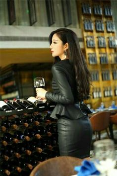 Asian girl in black leather peplum top and black leather skirt ensemble