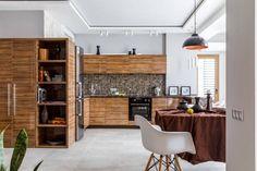 Nyitottan, mégis szépen elkülönített zónákkal kialakított 60m2-es modern, férfias lakás, gerendákkal elválasztott háló, fényes fa konyhabútor