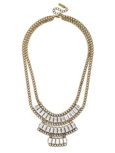 A three-tiered statement bib blends antiqued gold with crystal baguettes for a modern yet regal silhouette.