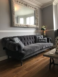 Grey interior design tweed tetrad parquet coffee table. Ornate large mirror, loaf bagsie sofa