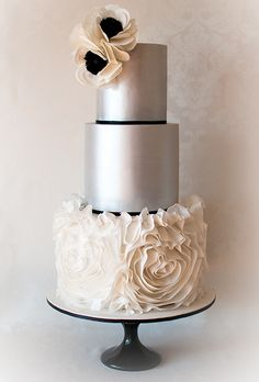 Brides.com: . A sophisticated Vera Wang wedding gown inspired this ultra-elegant lemon-cake confection from Yummy Cupcakes & Cakes, which features sleek silver tiers, swirls of ruffled rosettes, and striking sugar anemones. Price upon request, Yummy Cupcakes & Cakes