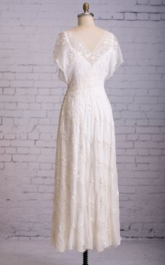 Vivian wedding dress from Martin McCrea. Full length back view. Flowing silk chiffon, embroidered and beaded. Asymmetrical wrap style bodice w/ kimono-style cap sleeves & side button closure. Slip dress of double silk satin. Color: Natural White