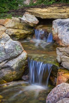 Moss covered rocks lend an aged appearance to this water feature.