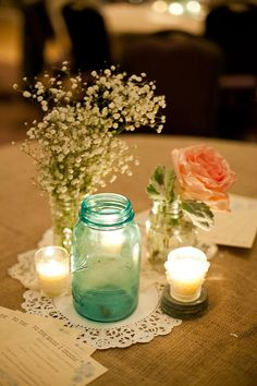 Wedding centerpiece : Burlap tablecloth, vintage doilies, blue Mason jars. Babies breath and garden roses.