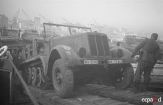 """In the port of Boulogne, the Germans practice loading vehicles on board landing craft as part of the preparations for Operation Sealion. The vehicle is an Sd.kfz.8 (Sonderkraftfahrzeug 8 - """"special motorized vehicle 8""""). This was a German half-track vehicle that saw widespread use in  WWII. Its main role was as a prime mover for heavy towed guns. Operation Sea Lion, Landing Craft, Ww2 Photos, Chenille, American War, German Army, Pearl Harbor, D Day, Armored Vehicles"""