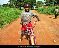 Boy riding bicycle along a dirt road on the outskirts of Gbarnga, Liberia Boy riding bicycle along a dirt road on the outskirts of Gbarnga, Liberia Boy riding bicycle along a dirt road on the outskirts of Gbarnga, Liberia © Tommy Trenchard / Alamy