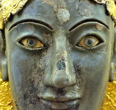 """Part of a """"chryselephantine"""" statue (gold and ivory). It is believed to be a gift from king Kroisos to Delphi and presumed to be Apollo. It was burned in a fire. He holds a shallow offering-bowl. The enigmatic smile is typical of the Archaic period of Greek art and was made in Ionia the 6th c BC."""