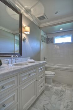 Classic white carrera marble bathroom. why a black frame mirror does not work with white cabinets.
