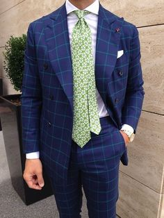 Shop this look on Lookastic:  https://lookastic.com/men/looks/double-breasted-blazer-dress-shirt-dress-pants-tie-pocket-square-watch/12352  — White Dress Shirt  — White and Green Print Tie  — White Pocket Square  — Blue Check Double Breasted Blazer  — Gold Watch  — Blue Check Dress Pants