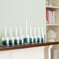 A fancy Hanukkah menorah can be expensive. But you can light the Night for a few dollars. Dollar store candles, glasses and BLUE stones or white stones. (Not sure why they used green here!) and you're set. You could even use river rocks. Just be sure the candles are securely set, and not too close to the wall!
