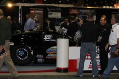 Guests gather around a racing car at the 2012 PRI show.