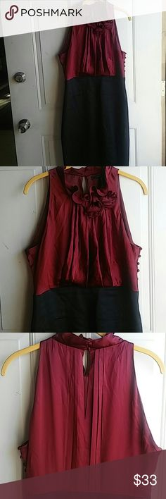 """BCBG.  MAXAZRIA  dress gently used. Clean and in good condition, has opening on top at back and two covered button for in and out plus 6 functioning side buttons and an 8 """" zipper on left side all shown in pics..  Nice ruffle and rose details in front at neckline.  Length from shoulder down 40"""" Waist about 16"""" across and armpit to armpit across about 19"""". There' s a slit at back of dress skirt hem.  Colored top 100% silk, there's 4"""" waist band black 100%silk.Bottom 76% acetate 20 polyester…"""
