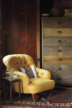 butter yellow comfy reading chair and soft stained chest of drawers