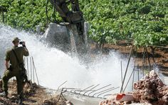 An Israeli soldier observes as a bulldozer destroys a water canal built by a Palestinian man on his land near the Jewish settlement of Qiryat Arba'a in Hebron in the occupied West Bank on June 8, 2009. Israeli forces arrested the landlord and demolished the canal, which was allegedly built illegally near the Jewish settlement