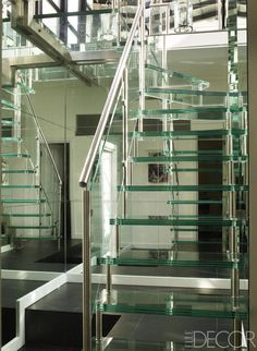 A custom staircase of steel and reinforced glass leads from the ground floor to the downstairs dining room and kitchen; the flooring is polished slate.