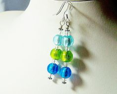 Sky Blue, Sea Green and deep Cobalt Blue foil-lined beads are separated with Clear sparkling Swarovski oval crystals. The earwires are sterling silver for your skin sensitive lobes and the 2 flowered silver rondelles on either end are silver-plated for your comfort.  These earrings are 2 long and when attached to the earwire, they will dangle almost 2+1/2 down making them some gorgeous shoulder dusters!  These are very lively, Spring and Summer earrings. Great for beach wear or to brighten…