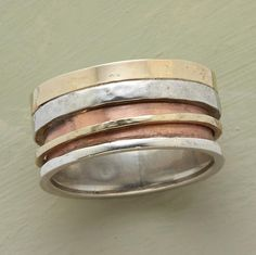 Mixed-metal band embraces a rotating ring of yellow gold, 14kt rose gold and sterling silver.