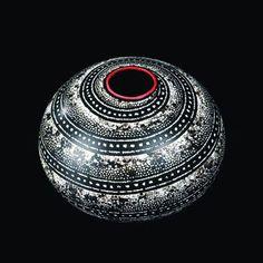 Design Jean Dunand (1877-1942)   Vase sphérique en dinanderie à corps très légèrement aplati, entièrement recouvert de laque noir à décor en spirales concentriques de rubans à décors géométriques incrustés de coquille d'œuf. Col rond, plat, souligné d'un filet de laque rouge (très léger saut de laque sur la face interne de l'épaisseur du col) et fond en laque rouge uni.