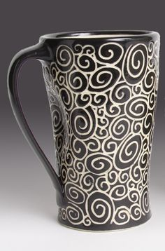 Doodle Mug by Jennifer Falter. A whimsical wheel thrown ceramic mug, decorated with sgraffito using black slip, featuring a pattern of spirals. Glazed to give a glossy finish. Each piece is unique, and will vary slightly from piece to piece. This mug holds approximately 16 oz. Dishwasher and microwave safe.