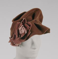 Woman's Hat  Designed by Simone Cange, French  Geography: Made in France, Europe Date: 1940s Medium: Pale brown wool felt, rose-brown silk velvet, and pink silk roses  Accession Number: 2001-122-10