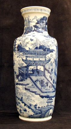 A Fine Large Kangxi Blue and White Porcelain Rouleau Vase c.1680-1700, Depicting the `West Lake`. Decorated with a Very Extensive Scene Covering the Surface of this Large Porcelain Vase. The Central Scene is of Two Scholars on Horseback, with Their Servants Carrying the Luggage, Arriving at a Large Building with People Awaiting their Arrival. This View is Part of a Wide Panorama of People Traveling by Horseback, Boat or Walking. There are Large Pavilions, Bridges, Jetties, Temples and…