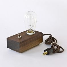 """Hand carved and crafted from off cuts, this red walnut base lamp features a large Edison light bulb, a silver toggle switch and a cotton power cord.   As simple as it gets.   Dimensions: 3"""" x 6"""" x 2"""""""