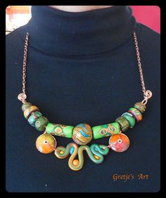 This ethnically inspired polymer clay necklace is constructed from a number of different kinds of my polymer beads. A large swirl-striped focal bead