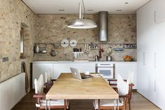 The original 16th century stone walls are left exposed in the kitchen. Tagged: Kitchen, Stone Slab Backsplashe, Laminate Counter, White Cabinet, Medium Hardwood Floor, Range Hood, Drop In Sink, Wall Oven, Cooktops, and Pendant Lighting. Photo 12 of 15 in A Spanish Architect Transforms a Medieval Townhouse Into a Stunning Rental