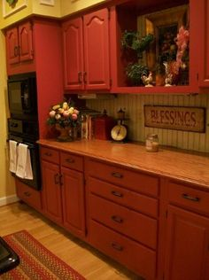 Love the countertop and red cabinets and the decor.
