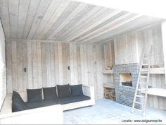 loungehoek in steigerhout met heerlijke kussens en buitenhaard