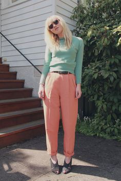 A 90's girl sporting a turtleneck and rolled-up salmon trousers.