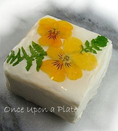 Yellow Violas on a small block of cream cheese.