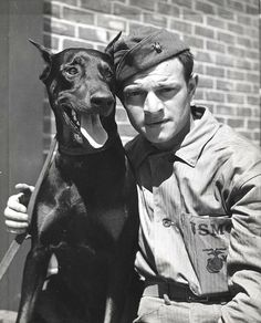 Private Alexander Boccardo and Doberman, ca. 1943 by Marine Corps Archives & Special Collections, via Flickr. During World War II Marine Devil Dogs learned the art of war at the Marine War Dog Detachment Training School at Camp Lejeune, North Carolina. These dogs were specifically trained to accompany Marines in landing operations, for sentry duty, deliver messages, and as scouts. In this photo, Private Alexander A. Boccardo is shown with his fighting partner, a Doberman Pincher.