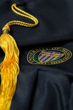 A graduation tassel and graduation robe lay next to each other commemorating a students journey through the University of Washington. #youW Photo by Luke Waters