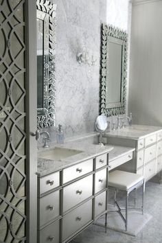 Glam bathroom features Venetian mirrors over his and her vanities with apothecary style drawers topped with marble accented with hook spout faucets flanking a drop-down, make-up vanity paired with x-based vanity stool against a backdrop of marble clad accent wall.