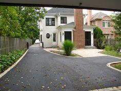 Asphalt driveway paving with brick border and stone patio